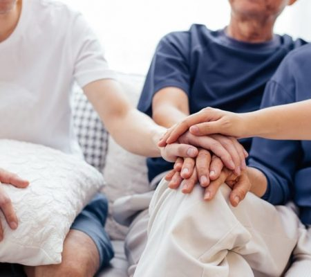 family-putting-hands-together-choosing-hospice-care-1024x585